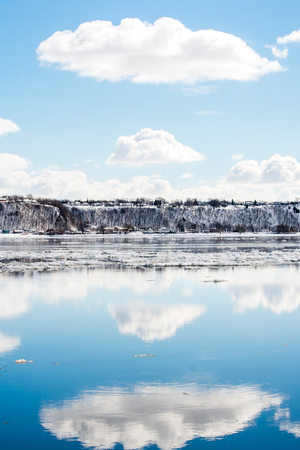 A clouds reflection in the river with floating ice, on a sunny day in Canada
