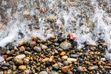 A wave on top of rocks or pebbles, bubbling up the beach at Lake Ontario