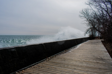 A wave breaking over the wall on a boardwalk, on Lake Ontario