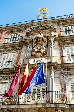 A building in Plaza Mayor in Madrid, Spain, with flags on the side of building Editorial