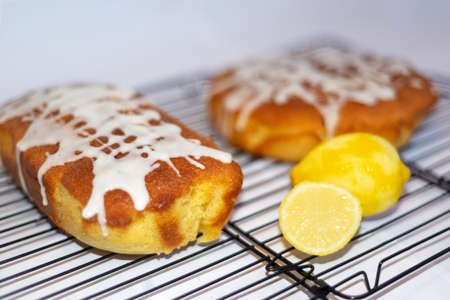 Two whole home made lemon drizzle cakes on a wire cake cooling rack