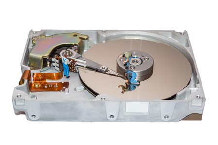 Miniature worker repair the hard drive. Hard disk isolated. The head of the hard drive is broken. Figure of little people. Employer. Recovery of computer data.
