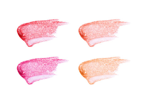 Different lip glosses isolated on white. Smudged lip gloss sample. Stock Photo