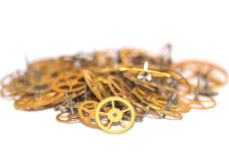 A pile of gear. Many mechanisms. Old vintage gears. Part of clockwork. The natural color and texture. Focus on front, blurred background. Golden cogs. Stock Photo