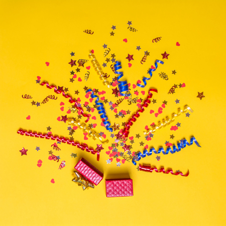 creativ: Creative concept with festive decor on yellow background. Confetti hearts and stars, red, yellow, blue ribbons fly out of the red gift box. Explosion of confetti.