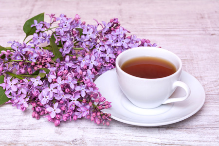 notepaper: White cup with coffee or tea and a bouquet of lilacs on a wooden background
