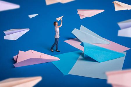 Creatief surrealismeontwerp met origami-papiervlakken. Jong meisje laat papieren vliegtuigen. Blauw, blauw, roze origami-ambachten.