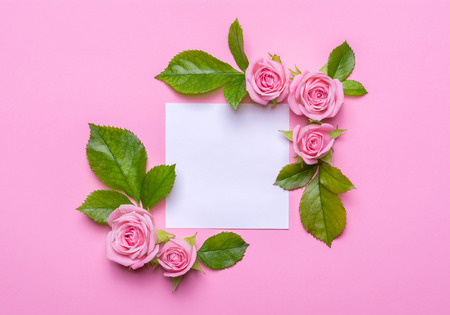 Floral frame with pink roses on a pink background. Corners borders of flowers with empty place for text. Background for invitation card. Flat lay design, view from above
