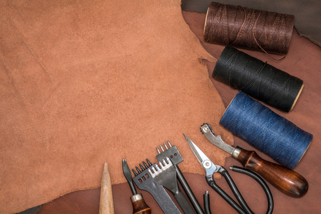 Tools for leather crafting and pieces of brown leather. Manufacture of leather goods. View from above. Empty space for text