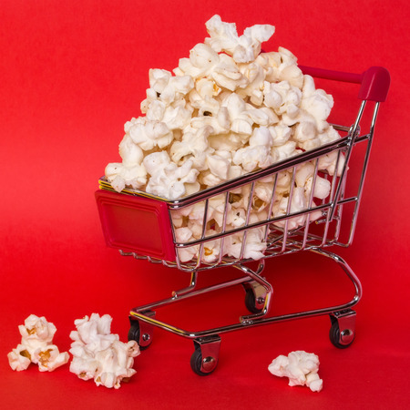 Popcorn in a shopping trolley. A bunch of popcorn on a red background. Surrealistic concept.
