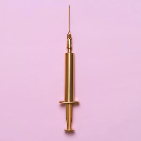 Golden syringe on a pink background. Medical item. Minimalism concept.