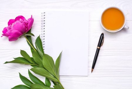 Empty notepad with place for text, pen, a cup of tea and peony flower on a white wooden background. Mockup for your design. View from above. Stock Photo - 105266600