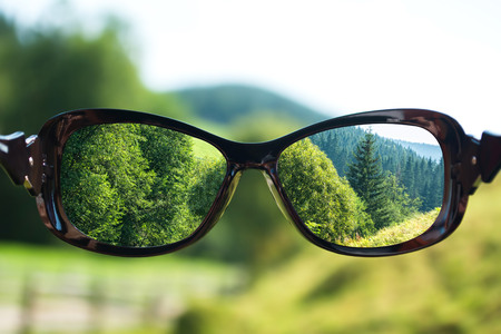 Creative concept about poor vision. Landscape focused in glasses lenses over the photo blurred Stock Photo