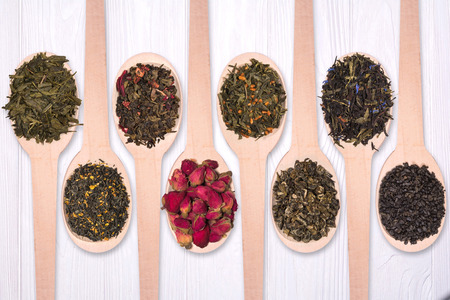 Set of dry herbal teas in wooden spoons on a white background. View from above 写真素材