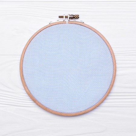 Tools for cross stitch. A hoop for embroidery and canvas on white wooden background. Mockup about hobby Stock Photo