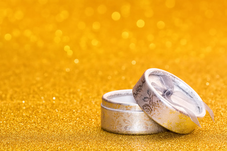 Silver gift box on a golden radiant background. Stock Photo
