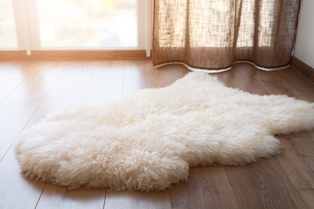 Sheep skin on the laminate floor in the room. Cozy place near the window. Sunny day