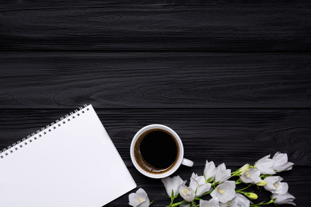 White flowers bells, coffee and empty notebook for your text on a black wooden background. Stock Photo