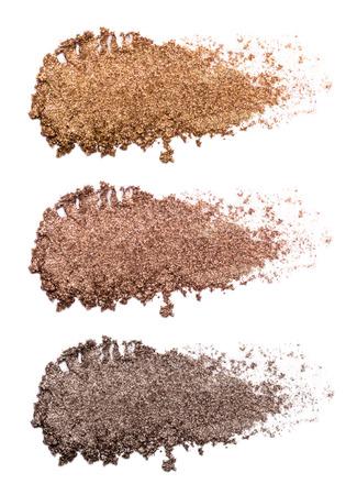Conjunto de trazos de sombra de ojos de bronce aislado sobre fondo blanco. Primer plano de un producto de maquillaje. Foto de archivo