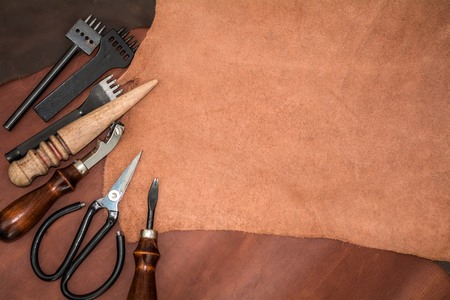 Pieces of leather and working tools. Craftmans workspace.