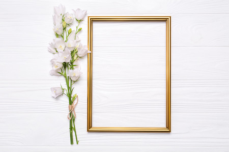 White flowers bells and a gold frame on a white wooden background. Mockup for your design Stock Photo