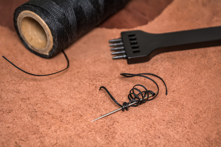 Natural leather, tool for creating products and bobbins of wax yarns. Stock Photo