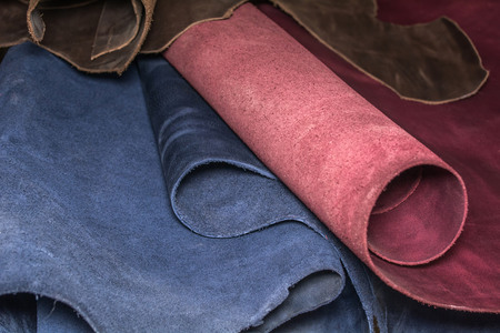 Rolls of natural brown, blue and purple leather. Materials for leather craft. Stock Photo