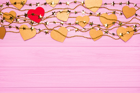 Flat lay border of red and gold hearts of confetti. Golden beads in the form of stars. Festive decor on a pink wooden background. View from above Stock Photo