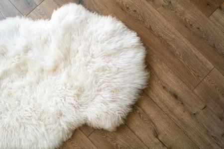 Piel de oveja en el suelo laminado de la habitación. Vista desde arriba.