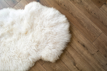 Sheep skin on the laminate floor in the room. View from above. Stock Photo