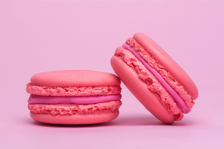 Two pink macaron cookies on a pink background.