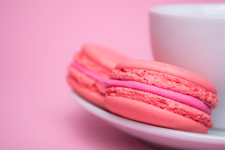 Two pink macaron cookies in a white saucer on pink background. Stock Photo
