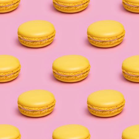 Seamless pattern with yellow macaron cookies on a pink background. Stock Photo