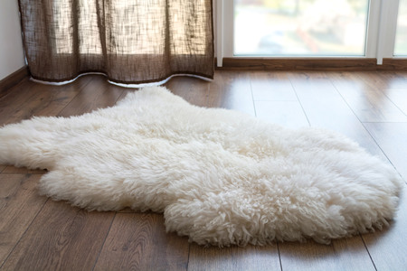 Sheep skin on the laminate floor in the room. Cozy place near the window