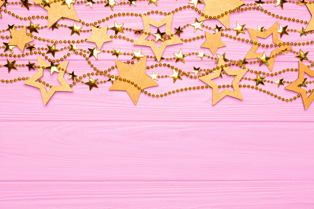 Flat lay border of big and small stars of confetti. Golden beads in the form of stars. Festive decor on a pink wooden background. View from above