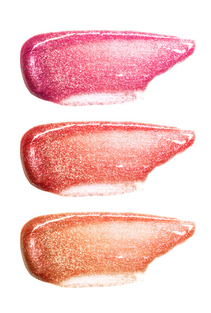Set of different colors lip glosses smear isolated on white. Smudged makeup product sample