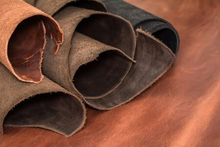 Rolls of natural brown and black leather. Materials for leather craft. Foto de archivo