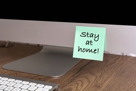 Computer with a sticker with the text Stay at home. Concept about quarantine and remote work.