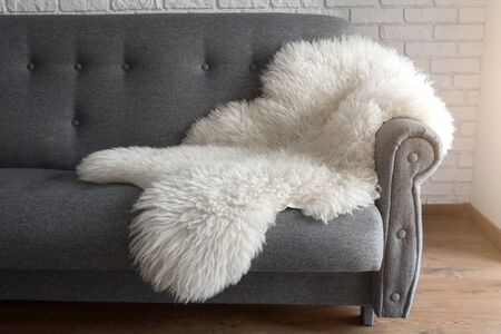 White sheep skin on a gray sofa. A cozy place to relax in the apartment. Modern Scandinavian style interior