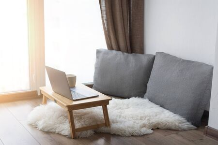 Work from home. Cozy workplace near the window for remote work and business online. Coffee table with a laptop. Quarantine concept.