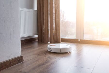 White robot cleaner on a wooden floor near the panoramic window. Household appliances for cleaning the house. Sunny day.