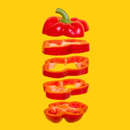 Creative concept with flying red capsicum. Sliced floating bell pepper on an orange background. Levity vegetable. Paprika with water drops