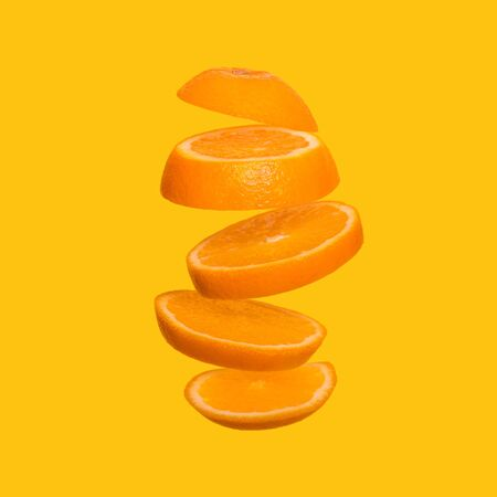 Creative concept with flying orange. Sliced orange on yellow background. Levity fruit floating in the air Stock fotó