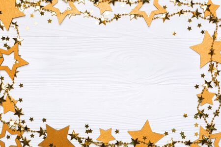 Flat lay frame of big and small stars of confetti. Golden beads of shine stars. Festive decor on a white wooden background. View from above. Stock fotó