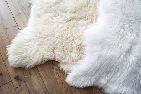 Natural sheep skin and synthetic on the laminate floor in the room. View from above. Comparison of natural and synthetic. Stock fotó