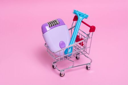 Purple epilator and blue razor in the supermarket trolley on a pink background. The concept of choosing a method of hair removal. Stock fotó