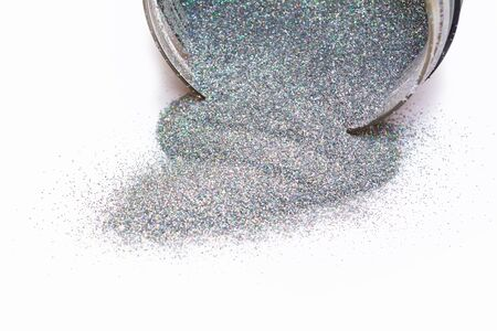 Holographic glitter powder spilled out of the can. Multicolor chrome texture. Sequins powder on white background.