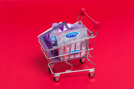 Kyiv, Ukraine - 21 May 2020: Durex condoms in a shopping trolley on the red background. Durex Elite and Invisible. Healthy and safe sex.