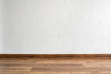Empty room with white wall and parquet. Minimal interior design.