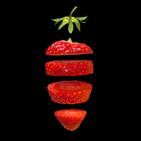 Strawberry slices isolated on black background. Surreal design. Pieces of fruit floating in the air.